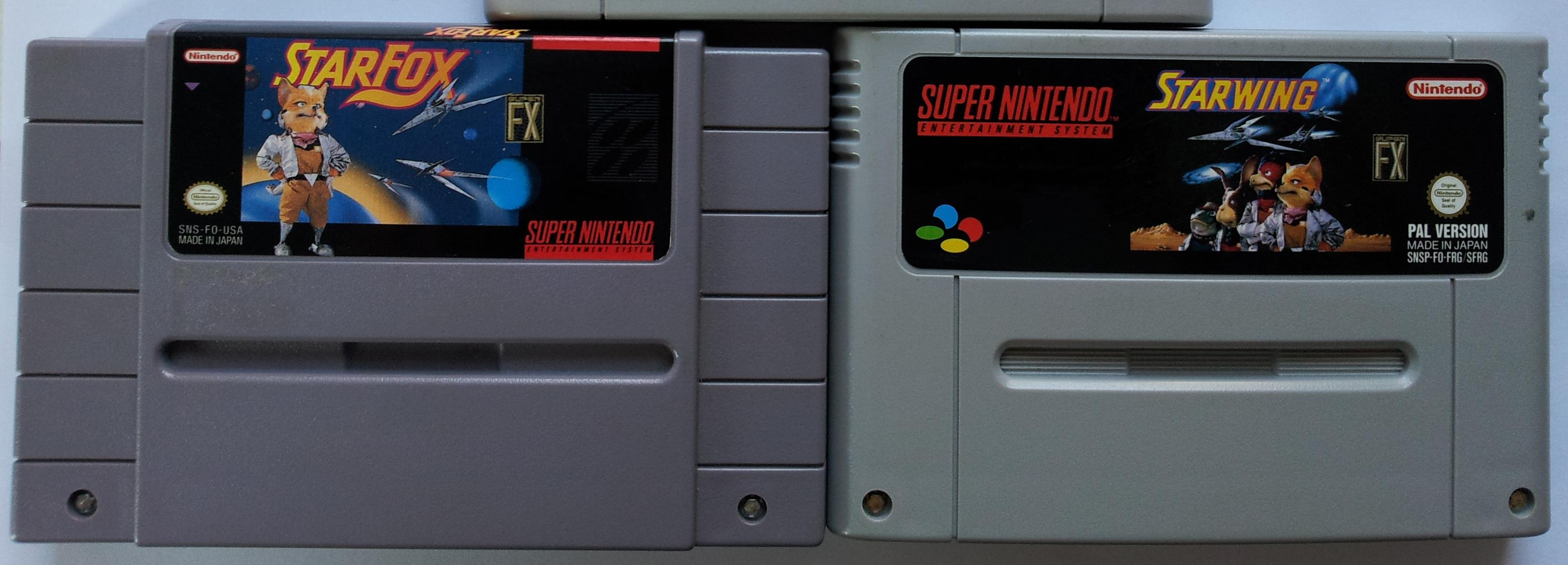 """Zwei Super NES-Module, eines (US-Cartridge) mit """"Star Fox""""-, eines (PAL-Cartridge) mit """"Starwing""""-Logo."""
